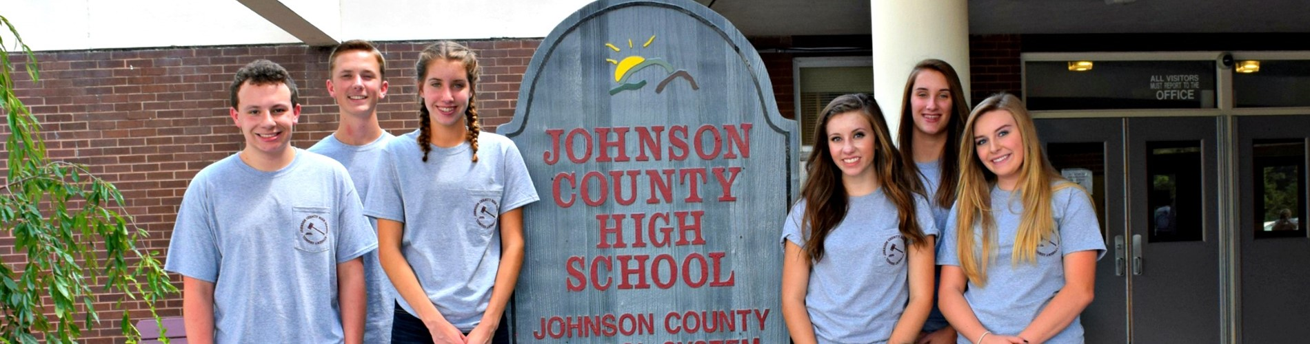 Students standing in front of the high school entrance sign